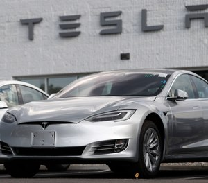 This July 8, 2018 photo shows a Tesla 2018 Model 3 sedans sitting on display outside a Tesla showroom in Littleton, Colo.
