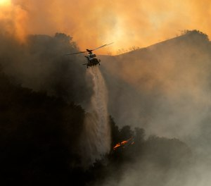A firefighting helicopter drops water onto a brush fire in the Pacific Palisades area of Los Angeles on Saturday, May 15. The Palisades Fire has burned more than 1,300 acres and forced the evacuation of about 1,000 Los Angeles residents.