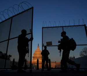 In this March 8, 2021, file photo, members of the National Guard open a gate in the razor wire topped perimeter fence around the Capitol at sunrise in Washington.