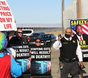 Special investigative services Lt. Armando Cervantes, right, films protesters at the Federal Correctional Institution at Mendota during a demonstration over staffing shortages, near the prison entrance in Mendota, Calif., Monday, May 17, 2021.