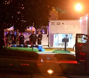 Police officers stand near the scene where three officers were fired upon late Wednesday, May 26, 2021, in Flower Mound, Texas.