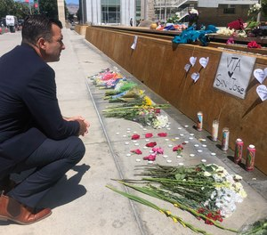 San Jose Mayor Sam Liccardo stops to view a makeshift memorial for the rail yard shooting victims in front of City Hall in San Jose, Calif., on Thursday, May 27, 2021.