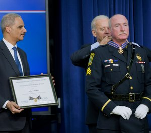 In this Feb. 11, 2015, file photo, Attorney General Eric Holder and Vice President Joe Biden award the Medal of Valor to Sgt. Jeffrey Pugliese from the Watertown, Mass., Police Department, during a ceremony in Washington.