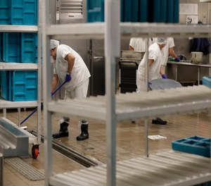 Workers are shown in the kitchen of the U.S. Immigration and Customs Enforcement detention facility in Tacoma, Wash.