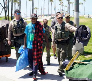 Members of the Los Angeles County Sheriffs Department's HOST, Homeless Outreach Service Team, walk with a homeless man in the Venice Beach section of Los Angeles.