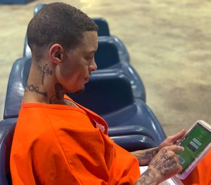 Inmate Byron Robinson works on a new Securus tablet, which are being provided for free to Oklahoma inmates as part of a new program by the Department of Corrections.