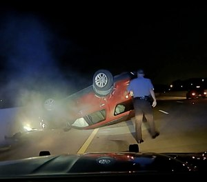 This screen shot taken from dash cam video owned by the Arkansas State Police shows trooper Rodney Dunn walking toward a flipped car in Pulaski County, Ark., on July 9, 2020.