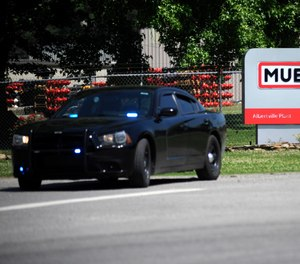 A police car guards the entrance to a Mueller Co. fire hydrant plant where police said multiple people were shot to death and others were wounded in Albertville, Ala., on Tuesday, June 15, 2021.