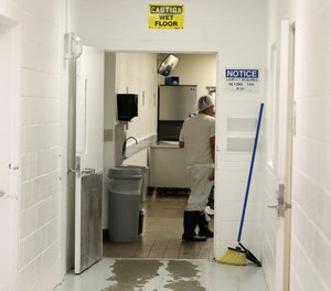 In this photo taken Sept. 10, 2019, a detainee works in a kitchen area at the GEO Group's immigration jail in Tacoma, Wash., during a media tour.