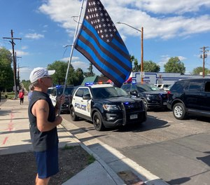 A man holds a blue line flag at the beginning of a line of about 30 police cars lined up for a procession in honor of the officer who was fatally shot in Arvada, Colo., on Monday, June 21, 2021.