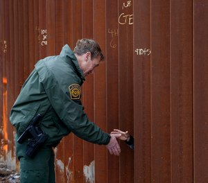 In this Jan 15, 2019, file photo, Rodney Scott, then-U.S. Border Patrol's San Diego sector chief shakes hands through a section of newly-replaced border wall in San Diego.