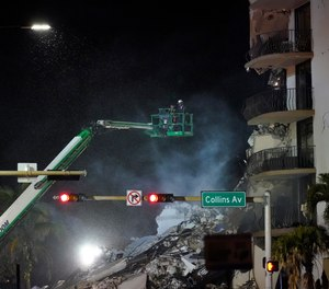 Workers ride in a lift as smoke rises off the rubble where a wing of a 12-story beachfront condo building collapsed, late on Thursday, June 24, 2021, in the Surfside area of Miami.