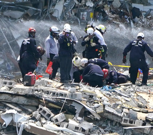 Rescue workers search the rubble of the Champlain Towers South condominium, Saturday, June 26, 2021, in the Surfside area of Miami. The building partially collapsed on Thursday.
