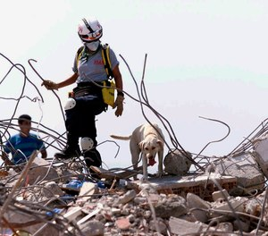 In this Aug. 23, 1999, file photo, Elena Lopez, of the Miami-Dade Fire Rescue, Florida Task Force One, Urban Search and Rescue team, searches the rubble in Izmit, Turkey, with her search dog
