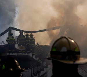 Firefighters stand at the smoldering aftermath of a fire that burned down the Evergreen Court Home for Adults, in Spring Valley, N.Y. Six people are facing charges in connection with the fire that killed a firefighter and a facility resident.