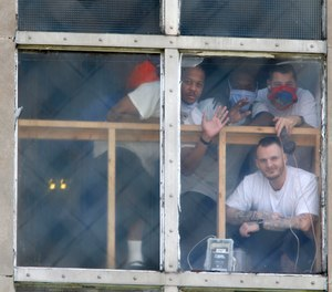 In this April 28, 2020, photo, inmates at the Westville Correctional Facility in Westville, Ind., watch protesters from a window. The protesters wanted better safety measures after an outbreak of COVID-19 cases at the prison.