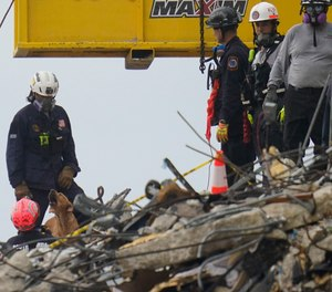 A dog working with search and rescue personnel barks to alert them after sniffing a spot atop the rubble at the Champlain Towers South condo building, where scores of people remain missing almost a week after it partially collapsed, Wednesday, June 30, 2021, in Surfside, Fla.