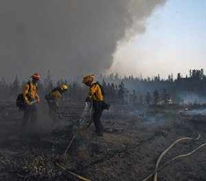 In this Monday, June 28, 2021, photo firefighters with the California Department of Forestry and Fire Protection work to extinguish hot spots after the Lava Fire burned through an area alongside U.S. Highway 97 northeast of Weed, Calif. A wildfire that has put thousands of people under evacuation orders in Northern California grew substantially but firefighters had some success against the flames, authorities said Wednesday, June 30. Burning in the shadow of the towering Mount Shasta volcano, the Lava Fire was ignited by lightning last week.