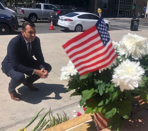 In this May 27, 2021, file photo, San Jose Mayor Sam Liccardo stops to view a makeshift memorial for the rail yard shooting victims in front of City Hall in San Jose, Calif.
