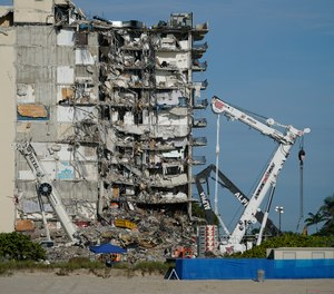 Workers peer up at the rubble pile at the partially collapsed Champlain Towers South condo building, on Thursday, July 1, 2021, in Surfside, Fla. Search and rescue workers, who have had to contend with summer rainstorms, fires within the debris, and the threat of collapse from the still standing portion of the building, were not visible atop the rubble on Thursday morning, as scores of people remain missing one week after the collapse.