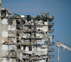 A parked crane sits beside the still standing section of Champlain Towers South, which partially collapsed last Thursday, as rescue efforts on the rubble below were paused out of concern about the stability of the remaining structure, Thursday, July 1, 2021, in Surfside, Fla. Scores of residents are still missing one week after the seaside condominium building partially collapsed.