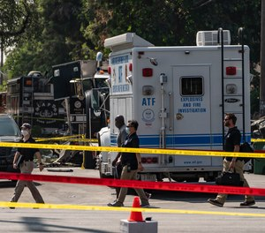 Investigators walk past an armored Los Angeles Police Department tractor-trailer Thursday, July 1, 2021 in Los Angeles, after a cache of homemade fireworks exploded during emergency response operations.