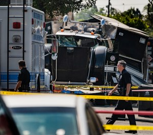 Police officers walk past the remains of an armored Los Angeles Police Department tractor-trailer Thursday morning July 1, 2021, after illegal fireworks seized at a South Los Angeles home exploded Wednesday evening, in South Los Angeles.