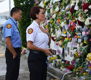 From left, Miami-Dade Fire Rescue personnel Fai Yeung and Chief Melanie C. Adams visit the makeshift memorial setup near the partially collapsed 12-story Champlain Towers South Condo in Surfside, Fla., Thursday, July 1, 2021. Search is paused because of structural concerns officials say. The apartment building partially collapsed on Thursday, June 24