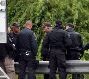 Police work on in the area of an hours long standoff with a group of armed men that partially shut down interstate 95, Saturday, July 3, 2021, in Wakefield, Mass.