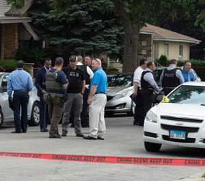 Chicago Police work on a crime scene in a residential neighborhood, Wednesday, June 7, 2021. Three undercover law enforcement officers were shot and wounded Wednesday morning while driving onto an expressway on Chicago's South Side.