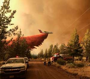 This photo provided by the Oregon Department of Forestry shows a firefighting tanker making a retardant drop over the Grandview Fire near Sisters, Ore., Sunday, July 11, 2021. The wildfire doubled in size to 6.2 square miles (16 square kilometers) Monday, forcing evacuations in the area, while the state's biggest fire continued to burn out of control, with containment not expected until November