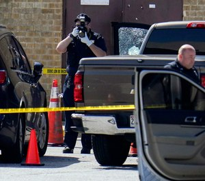 Shattered glass is seen on a pickup's driver side door as investigators document the scene in a mall parking area where two Baltimore city police officers were shot and a suspect was killed as a U.S. Marshals' task force served a warrant, Tuesday, July 13, 2021, in Baltimore, Md.