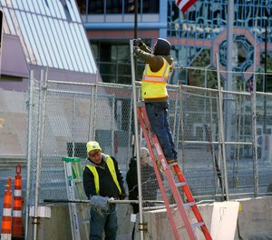 In this Wednesday, Feb. 23, 2021 file photo, workers install barbed wire on fencing outside the Hennepin County Government Center in Minneapolis, as part of security preparation for the trial of Derek Chauvin.