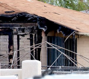 Tucson Police investigators work at the scene of a house fire where a body was found in Tucson, Ariz., Monday, July 19, 2021.
