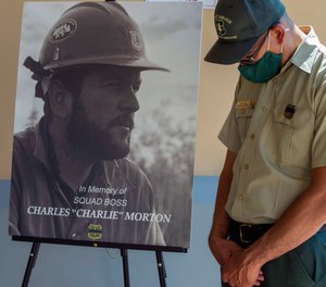 San Bernardino National Forest firefighter David Cruz lowers his head during a memorial for Charles Morton, the U.S. Forest Service firefighter assigned to the Big Bear Hotshots who was killed in the line of duty on the El Dorado Fire at The Rock Church in San Bernardino, Calif.