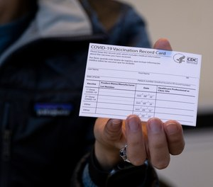 Auf diesem Aktenfoto vom 10. Januar 2021 hält eine Krankenschwester einen COVID-19-Impfausweis in einer Klinik in Brooklyn, New York.