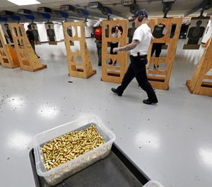 In this July 16, 2019, file photo, an officer taking part in training walks near a box of ammunition at the Washington State Criminal Justice Training Commission in Burien, Wash.