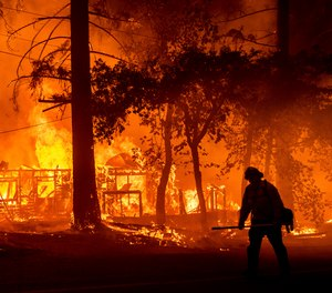 A firefighter passes a burning home as the Dixie Fire flares in Plumas County, Calif.
