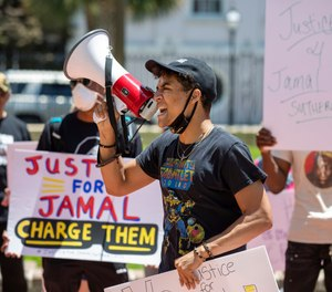 Elijah Whiteside leads protesters in a chant outside of Solicitor Scarlett Wilson's office in the Charleston County Judicial Center, Friday, May 21, 2021, in Charleston, S.C., to demand that the officers involved in the January death of Jamal Sutherland be charged.