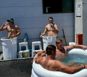 Members of Australia's men's rugby sevens team soak in ice baths following practice in the midday heat at the Tokyo 2020 Olympics, in Tokyo, Friday, July 23, 2021.
