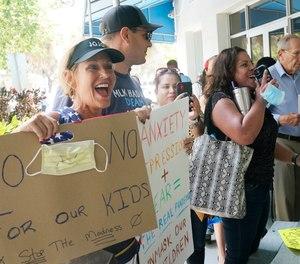 Joann Marcus of Fort Lauderdale, left, cheers as she listens to the Broward School Board's emergency meeting, Wednesday, July 28, 2021, in Fort Lauderdale, Fla.