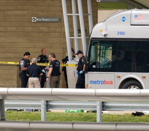 Police are looking at a scene and items are seen on the ground near a Metrobus outside the Pentagon Metro area, Tuesday, Aug. 3, 2021 at the Pentagon in Washington.