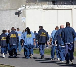 In this Feb. 26, 2013, file photo, inmates walk through the exercise yard at California State Prison Sacramento, near Folsom, Calif.