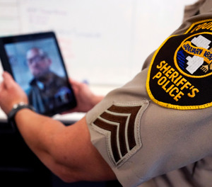 In this Friday, Aug. 13, 2021, photo Sheriff's Police Sgt. Bonnie Busching tests a virtual meeting with a tablet at the Cook County Sheriff's Office in Chicago.