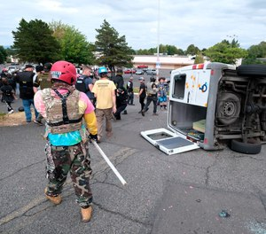 A van that was driven by anti-fascist protesters is pictured flipped on its side with all windows smashed after it was attacked for trying to drive into a Proud Boys rally Sunday, Aug. 22, 2021, in Portland, Ore.