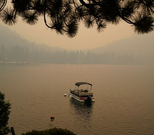 Smoke from the Caldor Fire, shrouds Fallen Leaf Lake near South Lake Tahoe, Calif., Tuesday, Aug. 24, 2021. The massive wildfire, that is over a week old, has scorched more than 190 square miles, (492 square kilometers) and destroyed hundreds of homes since Aug. 14. It is now less than 20 miles from Lake Tahoe.