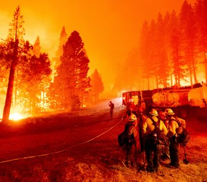 The Caldor Fire burns along both sides of Highway 50 as firefighters work to stop its eastward spread in Eldorado National Forest, Calif.