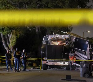 In this June 30, 2021 file photo ATF investigators stand next to the remains of an armored Los Angeles Police Department tractor-trailer after illegal fireworks seized at a home exploded in the containment chamber, in South Los Angeles.