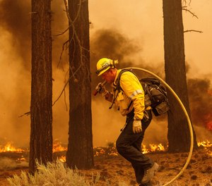 A firefighter battles the Caldor Fire along Highway 89, Tuesday, Aug. 31, near South Lake Tahoe, Calif.