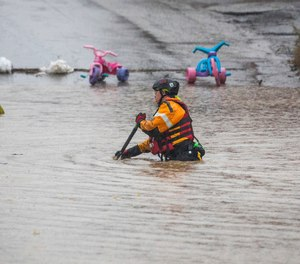 A member of a rescue team walks through a flooded street on Wednesday, Sept. 1, 2021, in Bridgeville, Pa. Pennsylvanians braced for downpours and high winds from the remnants of Hurricane Ida, with forecasters warning that creeks, streams and rivers would be inundated across the state's southern tier.
